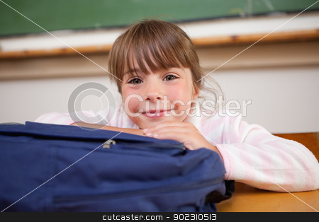 Cute schoolgirl posing with a bag stock photo, Cute schoolgirl posing with a bag in a classroom by Wavebreak Media