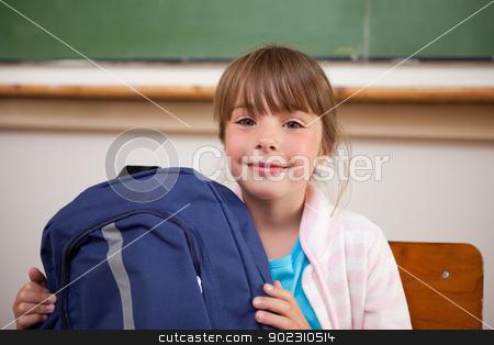 Happy schoolgirl posing with a bag stock photo, Happy schoolgirl posing with a bag in a classroom by Wavebreak Media