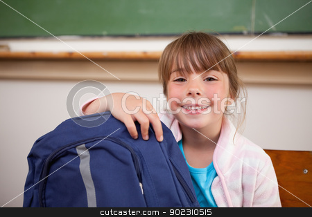 Smiling schoolgirl posing with a bag stock photo, Smiling schoolgirl posing with a bag in a classroom by Wavebreak Media