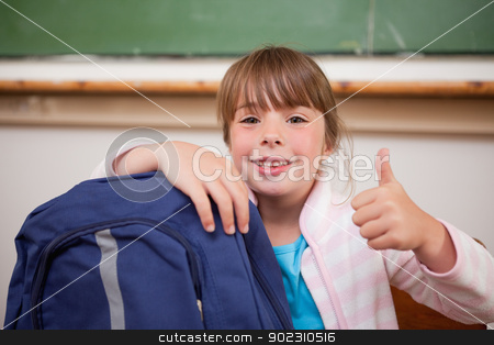 Smiling schoolgirl posing with a bag and the thumb up stock photo, Smiling schoolgirl posing with a bag and the thumb up in a classroom by Wavebreak Media
