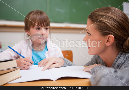 Schoolgirl writing a while her teacher is talking stock photo, Schoolgirl writing a while her teacher is talking in a classroom by Wavebreak Media