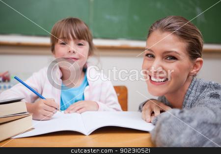 Schoolgirl writing with her teacher stock photo, Schoolgirl writing with her teacher in a classroom by Wavebreak Media