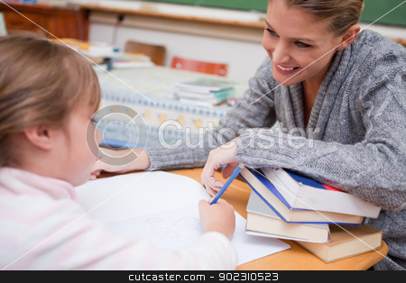 Schoolgirl writing with her smiling teacher stock photo, Schoolgirl writing with her smiling teacher in a classroom by Wavebreak Media