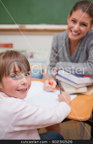 Portrait of a smiling teacher explaining something to her pupil stock photo, Portrait of a smiling teacher explaining something to her pupil in a classroom by Wavebreak Media