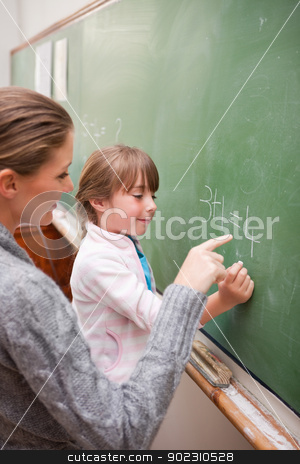 Portrait of a teacher and a pupil making an addition stock photo, Portrait of a teacher and a pupil making an addition on a blackboard by Wavebreak Media
