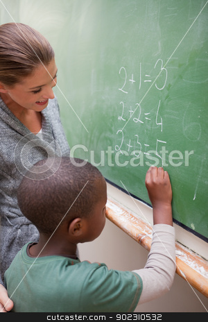 Portrait of a smiling teacher and a pupil making an addition stock photo, Portrait of a smiling teacher and a pupil making an addition in a classroom by Wavebreak Media