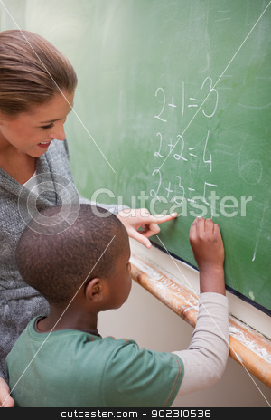 Portrait of a cute teacher and a pupil making an addition stock photo, Portrait of a cute teacher and a pupil making an addition on a blackboard by Wavebreak Media