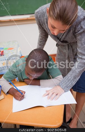 Portrait of a teacher explaining something to a focused schoolbo stock photo, Portrait of a teacher explaining something to a focused schoolboy in a classroom by Wavebreak Media