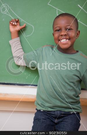 Portrait of a schoolboy showing something stock photo, Portrait of a schoolboy showing something on a blackboard by Wavebreak Media