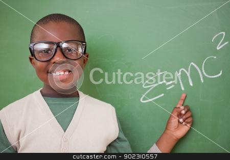 Smart schoolboy showing the the mass-energy equivalence formula stock photo, Smart schoolboy showing the the mass-energy equivalence formula on a blackboard by Wavebreak Media