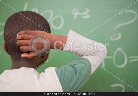 Schoolboy thinking with his hand on his head stock photo, Schoolboy thinking with his hand on his head in front of a blackboard by Wavebreak Media