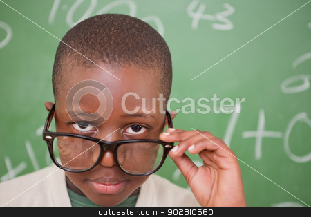 Schoolboy looking over his glasses stock photo, Schoolboy looking over his glasses in front of a blackboard by Wavebreak Media