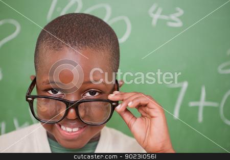 Smiling schoolboy looking over his glasses stock photo, Smiling schoolboy looking over his glasses in front of a blackboard by Wavebreak Media