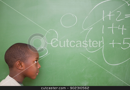 Schoolboy thinking about additions stock photo, Schoolboy thinking about additions in front of a blackboard by Wavebreak Media