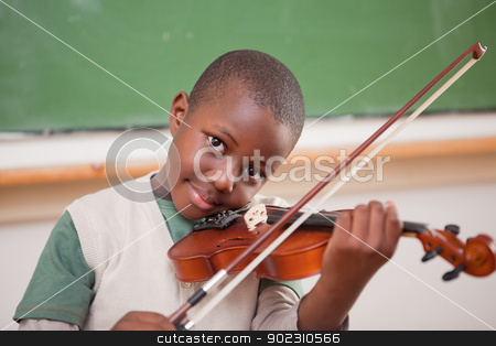 Schoolboy playing the violin stock photo, Schoolboy playing the violin in a classroom by Wavebreak Media