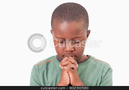 Young boy praying stock photo, Young boy praying against a white background by Wavebreak Media