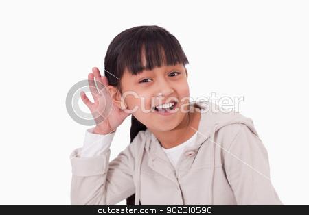 Girl pricking up her ear stock photo, Girl pricking up her ear against a white background by Wavebreak Media