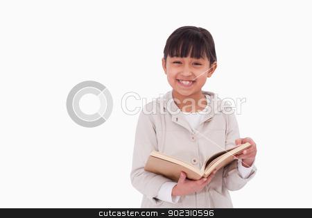 Smiling girl reading a book stock photo, Smiling girl reading a book against a white background by Wavebreak Media
