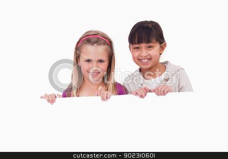 Girls behind a blank panel stock photo, Girls behind a blank panel against a white background by Wavebreak Media