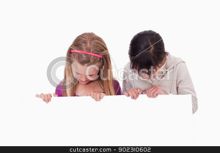 Girls looking at a blank panel stock photo, Girls looking at a blank panel against a white background by Wavebreak Media