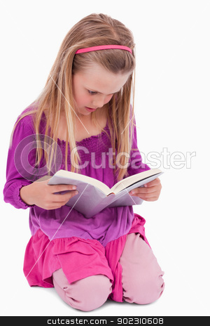 Portrait of a girl reading a book stock photo, Portrait of a girl reading a book against a white background by Wavebreak Media
