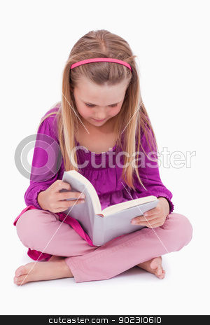 Portrait of a cute girl reading a book stock photo, Portrait of a cute girl reading a book against a white background by Wavebreak Media
