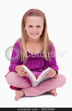 Portrait of a happy girl reading a book stock photo, Portrait of a happy girl reading a book against a white background by Wavebreak Media