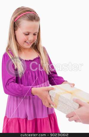 Portrait of a girl receiving a present stock photo, Portrait of a girl receiving a present against a white background by Wavebreak Media
