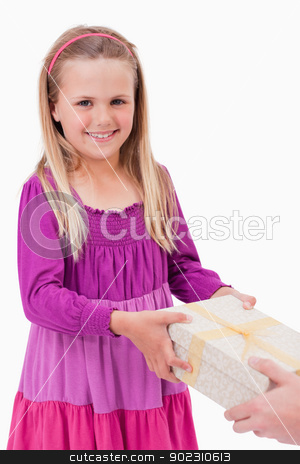 Portrait of a happy girl receiving a present stock photo, Portrait of a happy girl receiving a present against a white background by Wavebreak Media