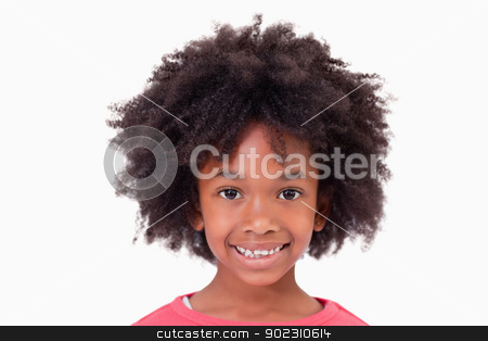 Close up of a smiling girl stock photo, Close up of a smiling girl against a white background by Wavebreak Media