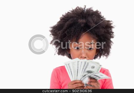 Girl looking at bank notes stock photo, Girl looking at bank notes against a white background by Wavebreak Media