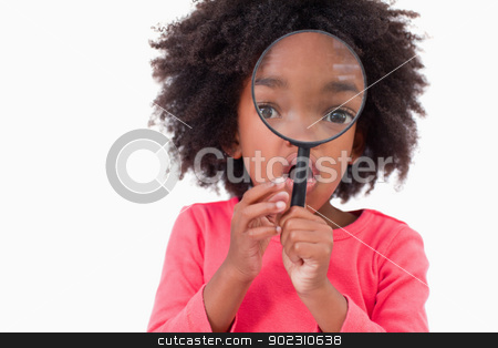 Girl looking through a magnifying glass stock photo, Girl looking through a magnifying glass against a white background by Wavebreak Media