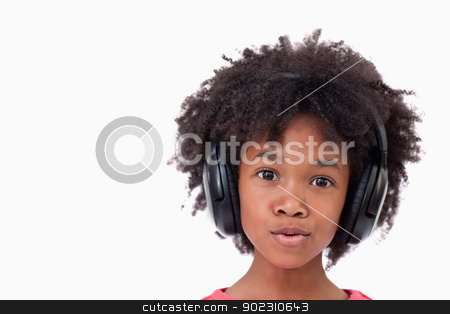 Close up of a girl listening to music stock photo, Close up of a girl listening to music against a white background by Wavebreak Media