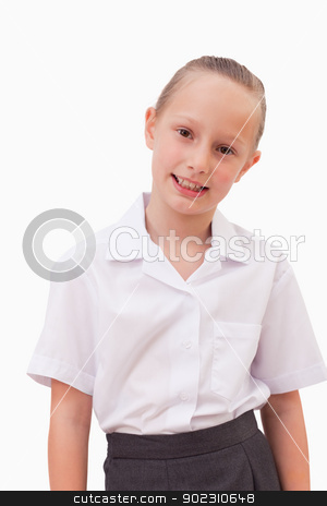 Portrait of a serious girl smiling stock photo, Portrait of a serious girl smiling against a white background by Wavebreak Media