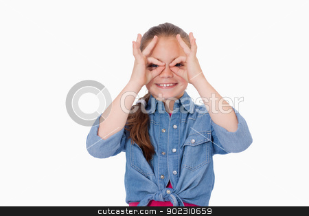 Girl with her fingers around her eyes stock photo, Girl with her fingers around her eyes against a white background by Wavebreak Media