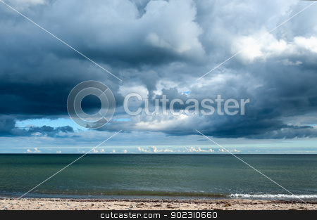 Storm clouds gathering over the ocean stock photo, View across a deserted sandy beach of cumulonimbus storm clouds gathering over the ocean by Kai Schirmer