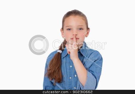 Girl asking for silence stock photo, Girl asking for silence against a white background by Wavebreak Media