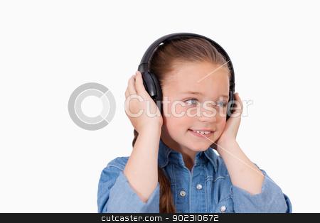 Smiling girl listening to music stock photo, Smiling girl listening to music against a white background by Wavebreak Media