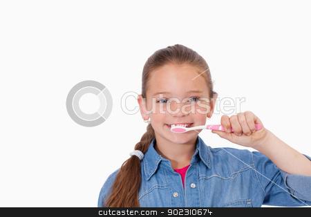 Healthy girl brushing her teeth stock photo, Healthy girl brushing her teeth against a white background by Wavebreak Media