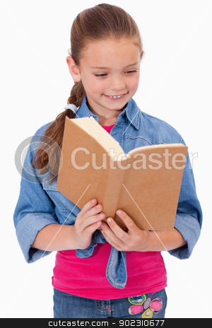 Portrait of a calm girl reading a book stock photo, Portrait of a calm girl reading a book against a white background by Wavebreak Media