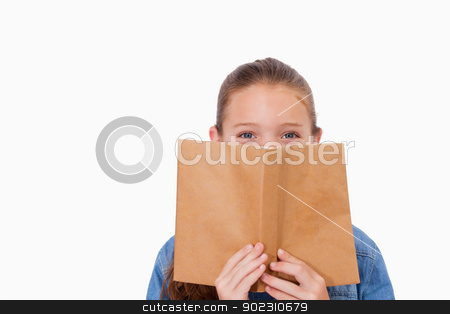 Girl hiding her face behind a book stock photo, Girl hiding her face behind a book against a white background by Wavebreak Media
