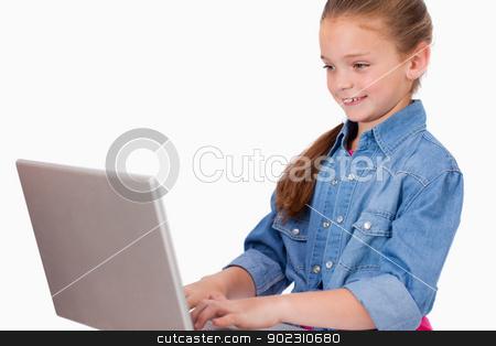 Smiling girl using a laptop stock photo, Smiling girl using a laptop against a white background by Wavebreak Media