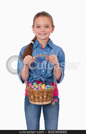 Portrait of a girl holding a basket full of Easter eggs stock photo, Portrait of a girl holding a basket full of Easter eggs against a white background by Wavebreak Media