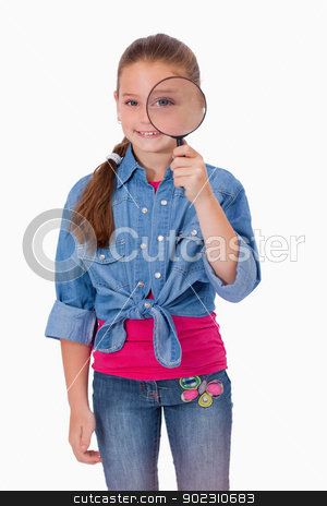 Portrait of a girl looking through a magnifying glass stock photo, Portrait of a girl looking through a magnifying glass against a white background by Wavebreak Media