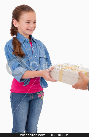 Portrait of a girl receiving a gift stock photo, Portrait of a girl receiving a gift against a white background by Wavebreak Media