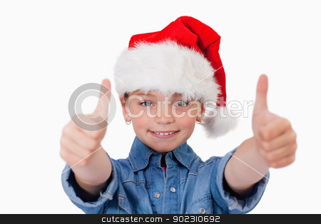 Girl with a Christmas hat and the thumbs up stock photo, Girl with a Christmas hat and the thumbs up against a white background by Wavebreak Media