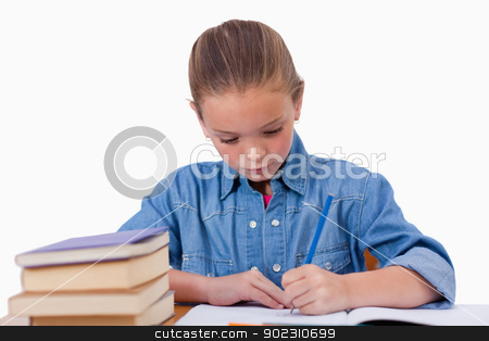 Serious girl writing on a notebook stock photo, Serious girl writing on a notebook against a white background by Wavebreak Media