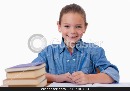 Smiling girl writing on a notebook stock photo, Smiling girl writing on a notebook against a white background by Wavebreak Media