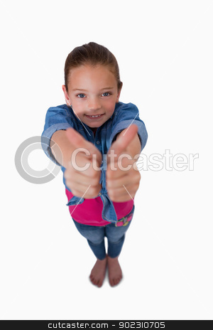 Portrait of a playful girl with the thumbs up stock photo, Portrait of a playful girl with the thumbs up against a white background by Wavebreak Media