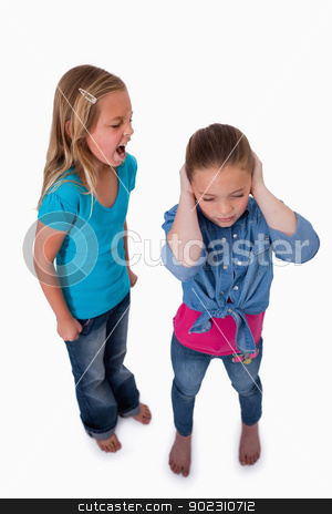 Portrait of an unhappy girl screaming at her friend stock photo, Portrait of an unhappy girl screaming at her friend against a white background by Wavebreak Media